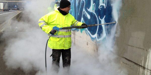 betonnen muur dat wordt gereinigd van graffiti